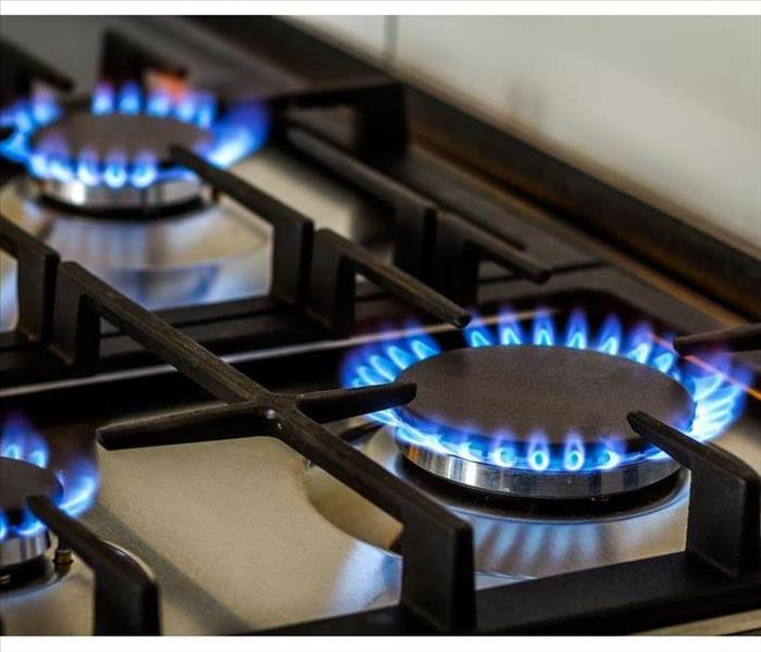 Natural gas burning on kitchen gas stove in the dark.