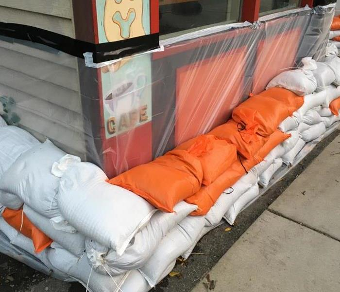 Outside of a business preparing for a storm with orange and white sand bags.