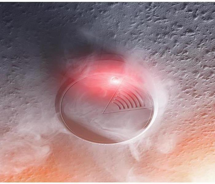 Smoke surrounding a smoke alarm that's going off